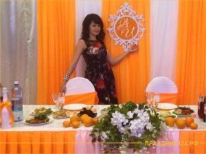 Ведущая на свадьбу на фоне оформленного зала в оранжевом цвете