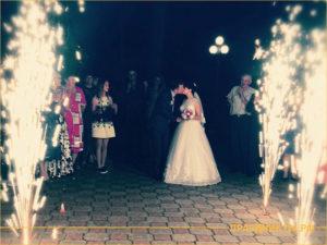Молодожены целуются на фоне огненных фейерверков