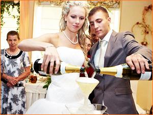Молодожены наливают шампанское в бокал на свадьбе