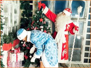 Дед Мороз и Снегурочка раскладывают подарки под елку