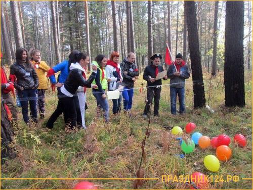 Люди играют в игру в осеннем лесу и лопают шарики