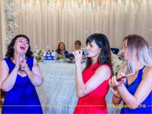 Ведущая праздников в красном платье и девушки в синем