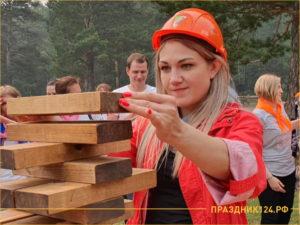 Девушка на корпоративе складывает пирамиду из дерева