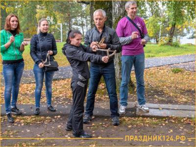 Девушка стреляет из рогатки по мешеням