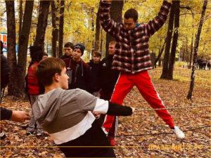 Компания людей играют в веревочный курс в осеннем лесу.