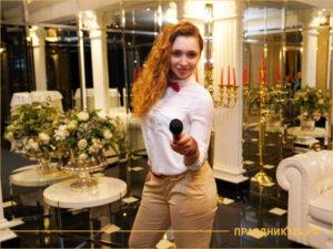 Девушка-ведущий в белой блузке с микрофоном