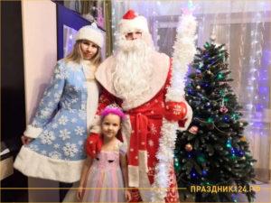 Дед Мороз и Снегурочка возле елки с ребенком